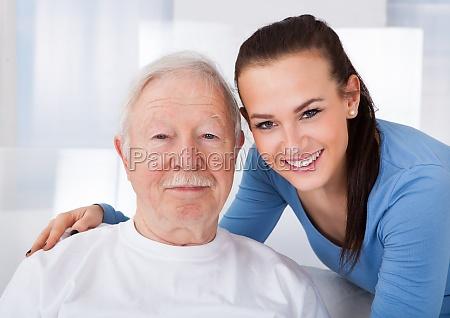 caretaker with senior man at nursing