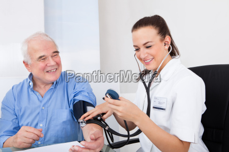 doctor, measuring, blood, pressure, of, senior - 12554692