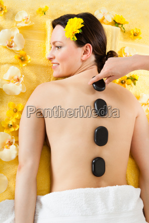 woman receiving hot stone therapy in