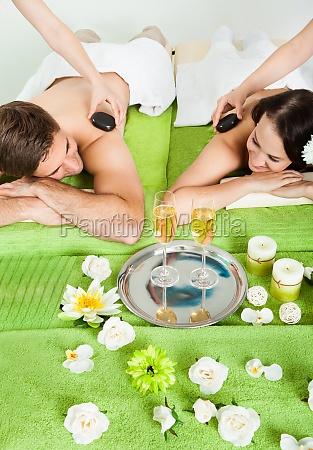 couple enjoying hot stone massage at