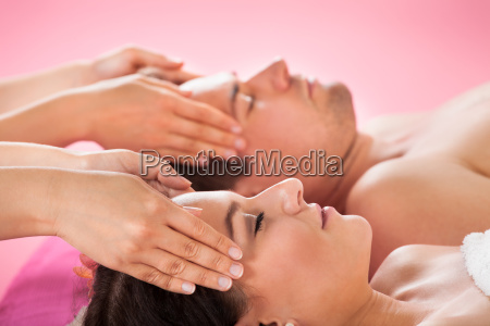relaxed couple receiving head massage at