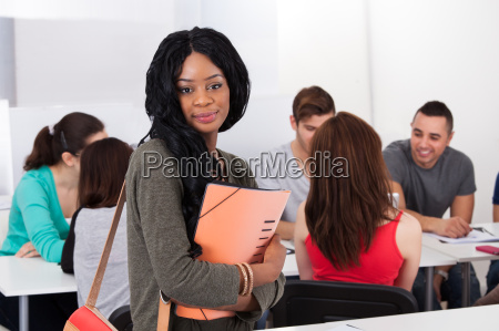 confident student holding file in classroom
