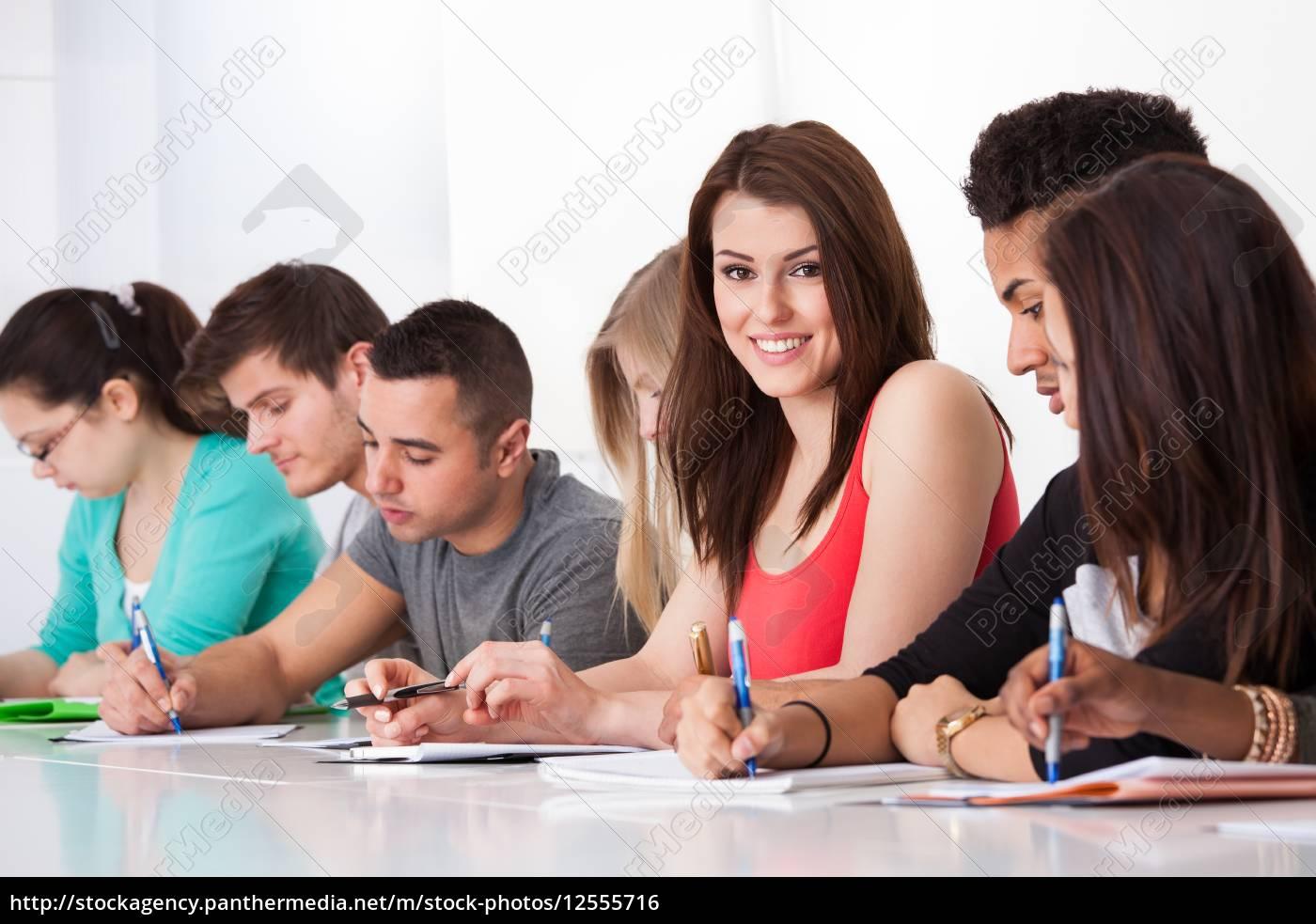 beautiful, student, sitting, with, classmates, writing - 12555716