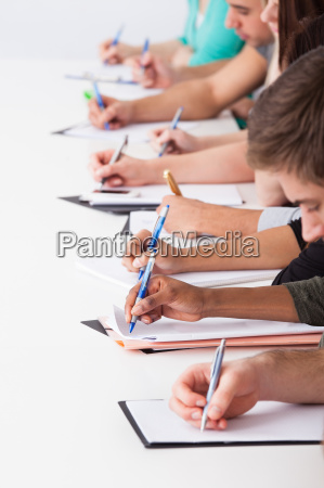 university, students, writing, at, desk - 12555726