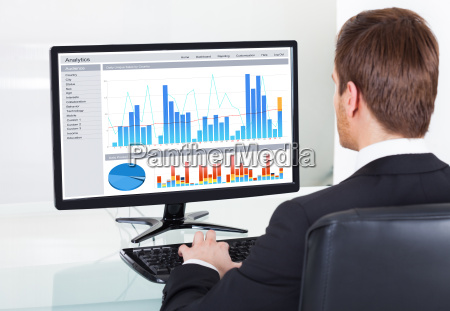 businessman, analyzing, graphs, on, computer, at - 12556800