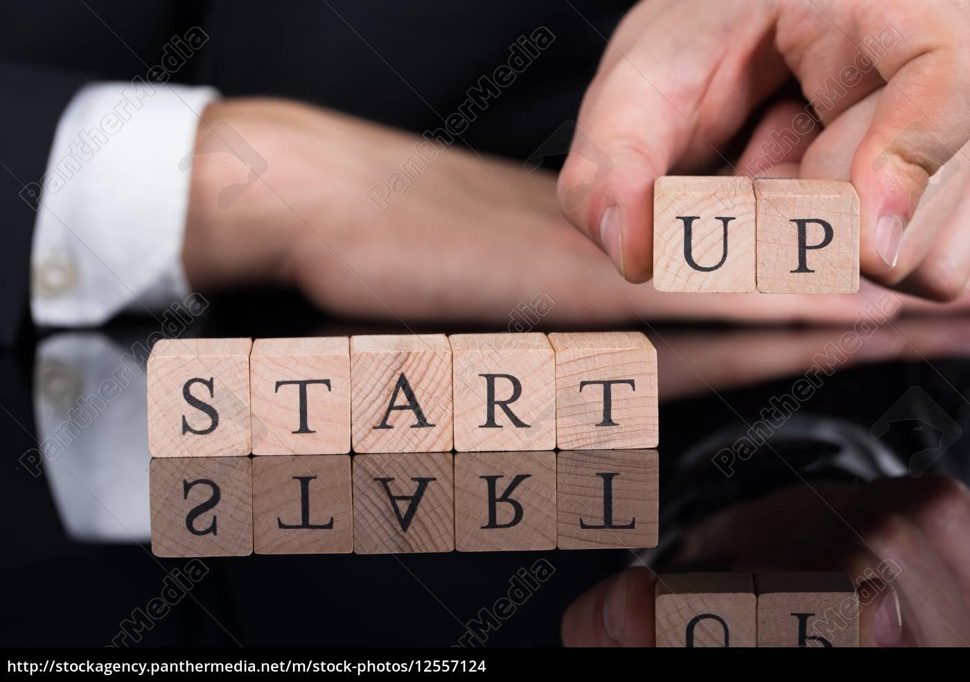 businessman, arranging, startup, blocks, on, desk - 12557124