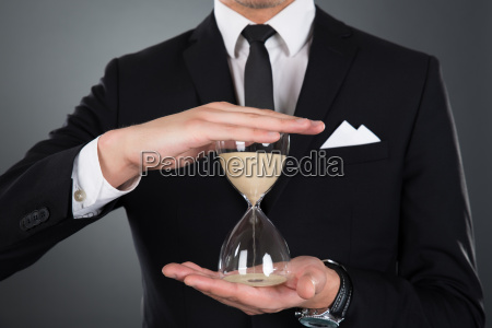 businessman, holding, hourglass - 12557068