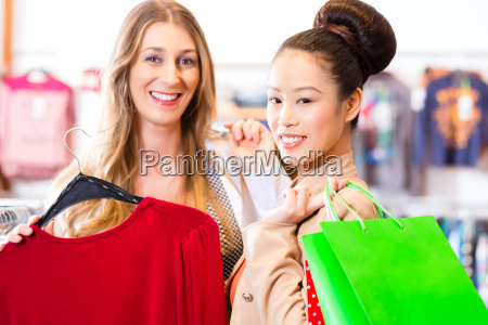 girlfriends shopping clothes in shop
