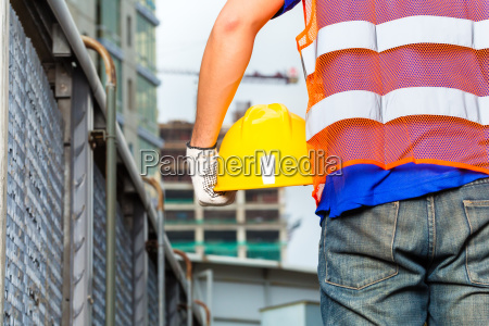 worker, on, construction, site, with, helmet - 12558636
