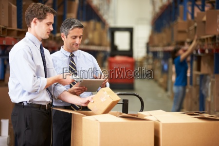 businessmen checking boxes with digital tablet