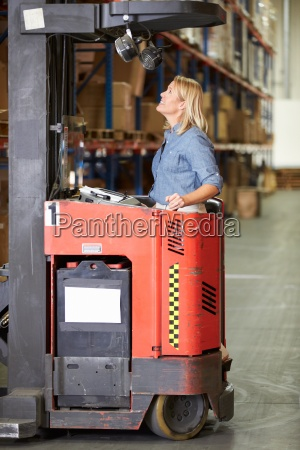 woman driving fork lift truck in