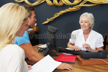 hotel receptionist helping couple to check
