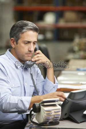 manager, working, at, desk, in, warehouse - 12564098