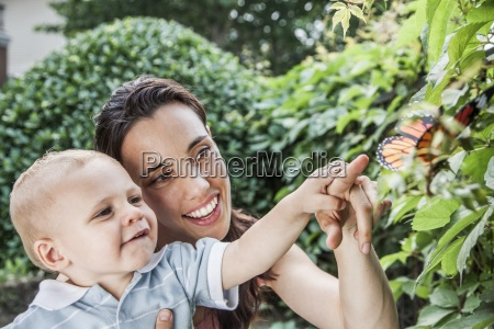 leisure activity two people pointing butterfly