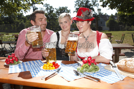 three bavarians in traditional costumes sitting