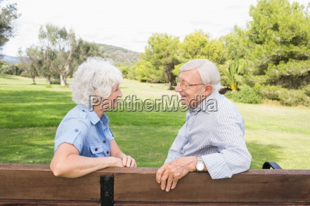 elderly couple chatting together on park
