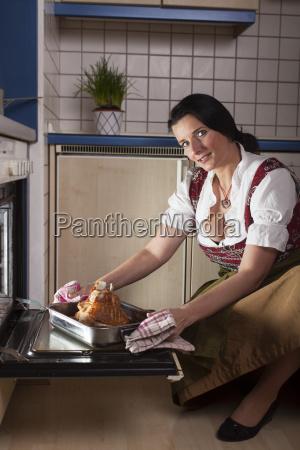bayerische frau mit einer schweinshaxe