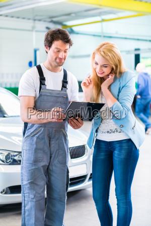 auto repair mechanic handing car at