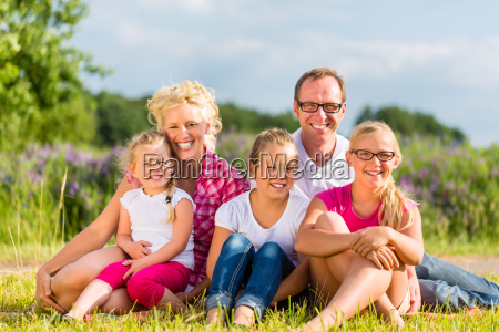 family sitting in the grass on