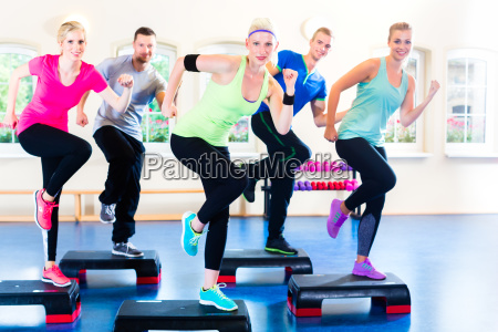 group at step workout in gym