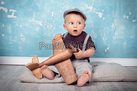 little boy playing with wooden flyer