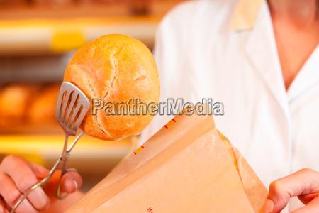 baker selling bread in basket in