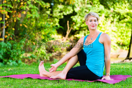 young woman in nature doing yoga