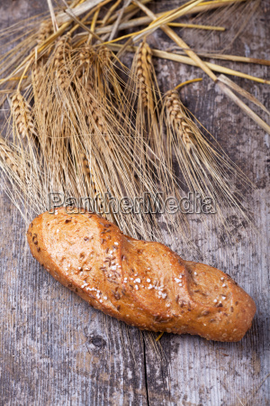 bread with wheat on wood