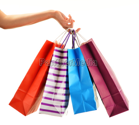 female hand holding paper shopping bags