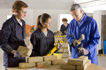teacher teaching students bricklaying in vocational