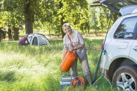 senior couple unpacking car for camping