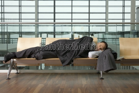 a businessman asleep in airport lounge