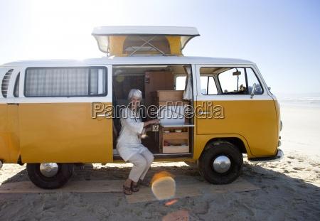 senior woman making tea in camper