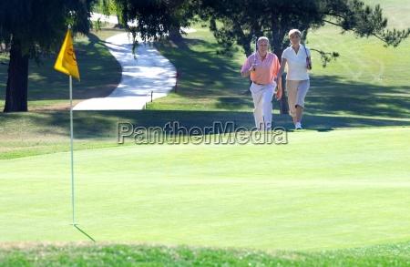 mature couple playing golf approaching putting