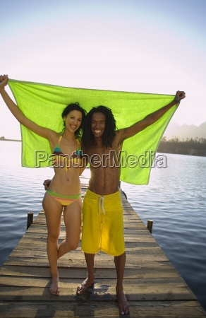 couple standing on lake jetty arms
