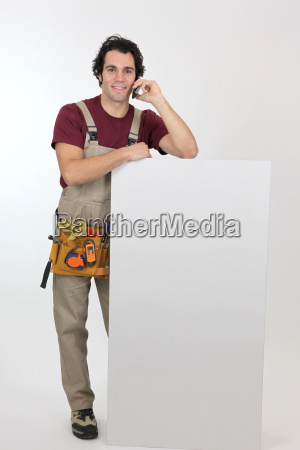 handyman on phone with white panel