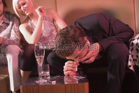 man snorting drugs at a nightclub