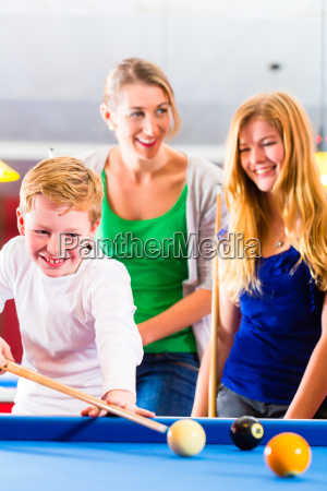 boy playing billiards with family