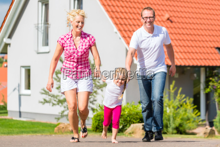family walking in front of house