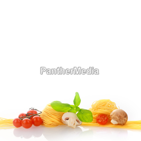 fresh pasta and vegetables on white