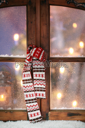christmas scarf hanging at window pane
