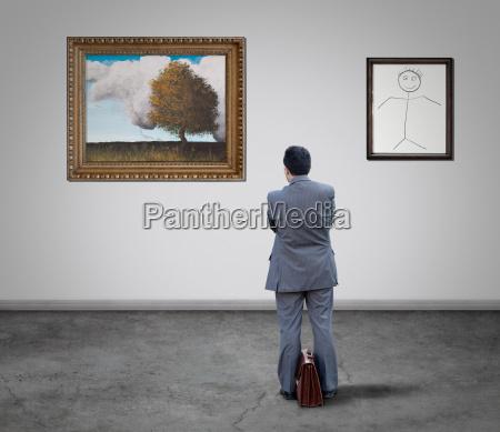 businessman looking paintings