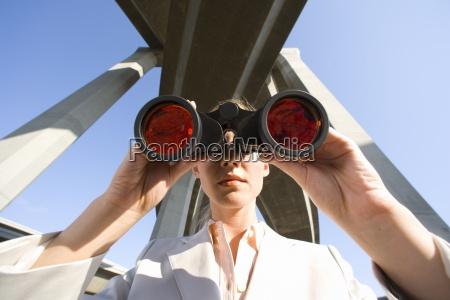 businesswoman using binoculars beneath overpasses close