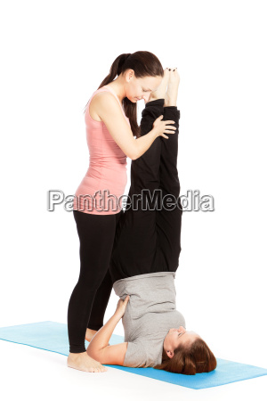yoga teacher gives assistance in a