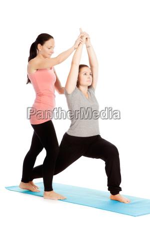 yogalehrerin gibt hilfestellung beim training virabhadrasana
