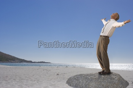 businessman standing on beach with arms