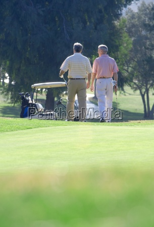 two mature men leaving putting green