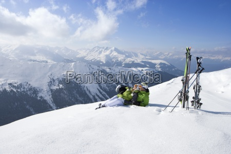 couple laying in snow on mountain