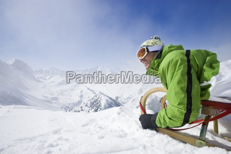 smiling man with sled on mountain