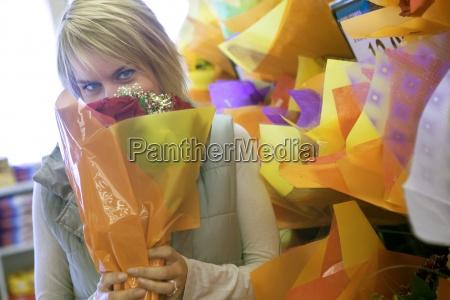 woman smelling flower bouquet beside shop